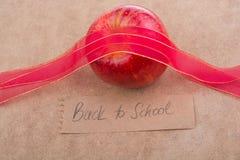 Πίσω στη σχολική εγγραφή με το μήλο και μια κορδέλλα Στοκ Φωτογραφίες