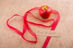 Πίσω στη σχολική εγγραφή με το μήλο και μια κορδέλλα Στοκ εικόνα με δικαίωμα ελεύθερης χρήσης