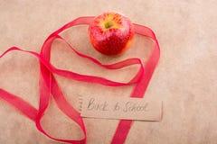 Πίσω στη σχολική εγγραφή με το μήλο και μια κορδέλλα Στοκ φωτογραφία με δικαίωμα ελεύθερης χρήσης