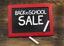 Πίσω στη σχολική πώληση στον ξύλινο πίνακα κιμωλίας πλαισίων με τις κιμωλίες Στοκ φωτογραφία με δικαίωμα ελεύθερης χρήσης