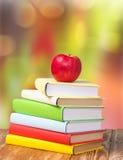 Πίσω στο μήλο βιβλίων σωρών υποβάθρου διακοπών σχολικού Σεπτεμβρίου Στοκ Φωτογραφία