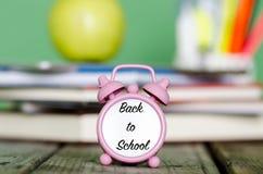 Πίσω στο σχολείο που γράφεται με το Μαύρο στο μικρό ρολόι με το σωρό του BO Στοκ φωτογραφία με δικαίωμα ελεύθερης χρήσης