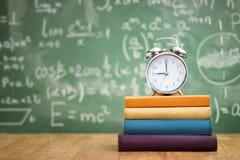 Πίσω στο σχολείο, τα βιβλία και ένα ξυπνητήρι στοκ εικόνα με δικαίωμα ελεύθερης χρήσης