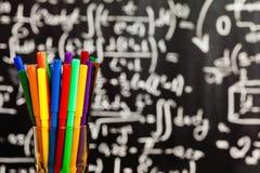 Πίσω στο σχολείο το υπόβαθρο με το σχολικό λεωφορείο και το σχολείο γράφεται από τις ζωηρόχρωμες κιμωλίες στο μαύρο σχολικό πίνακ Στοκ Φωτογραφία