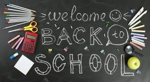` Πίσω στο σχολείο ` χειρόγραφο με τις σχολικές προμήθειες σε ένα μαύρο υπόβαθρο στοκ εικόνες