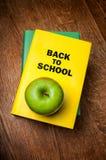 Πίσω στο σχολικό βιβλίο με ένα μήλο Στοκ φωτογραφία με δικαίωμα ελεύθερης χρήσης