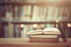 πίσω σχολείο έννοιας σωρός των βιβλίων πέρα από το ξύλινο γραφείο μπροστά από τη βιβλιοθήκη και των ραφιών με τα βιβλία Στοκ Φωτογραφία