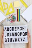 πίσω σχολείο έννοιας Τα θηλυκά χέρια κρατούν το σύγχρονο πίνακα με τις επιστολές από το Α στο Ω πέρα από το άσπρο ξύλινο υπόβαθρο στοκ εικόνες με δικαίωμα ελεύθερης χρήσης