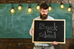 πίσω σχολείο έννοιας Το άτομο με τη γενειάδα και mustache στο έκπληκτο πρόσωπο καλωσορίζει τους σπουδαστές, πίνακας κιμωλίας στο  Στοκ Εικόνα