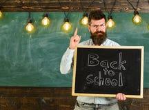 πίσω σχολείο έννοιας Το άτομο με τη γενειάδα και mustache στο ακριβές πρόσωπο προειδοποιεί τους σπουδαστές, πίνακας κιμωλίας στο  Στοκ φωτογραφία με δικαίωμα ελεύθερης χρήσης