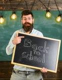 πίσω σχολείο έννοιας Το άτομο με τη γενειάδα και mustache στο εύθυμο πρόσωπο καλωσορίζει τους σπουδαστές, πίνακας κιμωλίας στο υπ Στοκ Εικόνα