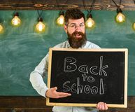 πίσω σχολείο έννοιας Το άτομο με τη γενειάδα και mustache στο εύθυμο πρόσωπο καλωσορίζει τους σπουδαστές, πίνακας κιμωλίας στο υπ Στοκ εικόνα με δικαίωμα ελεύθερης χρήσης