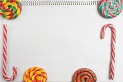 πίσω σχολείο ανασκόπησης ζωηρόχρωμα γλυκά candys στο κενό σημειωματάριο με τη σπείρα ριγωτοί κάλαμοι και σπείρα καραμελών lollipo στοκ φωτογραφίες
