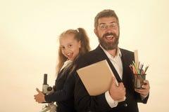 πίσω σχολείο Μικροσκόπιο λαβής παιδιών και μπαμπάδων, βιβλίο και χαρτικά Στοκ Φωτογραφία