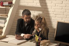 πίσω σχολείο Το κορίτσι και το άτομο κάθονται στο γραφείο και εξετάζουν το μικροσκόπιο Στοκ φωτογραφία με δικαίωμα ελεύθερης χρήσης