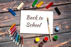 πίσω σχολείο έννοιας ανα&si Σχολικές προμήθειες και μαξιλάρι σκίτσων με πίσω στη σχολική επιγραφή Στοκ εικόνα με δικαίωμα ελεύθερης χρήσης