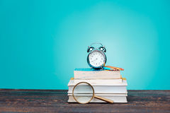 πίσω σχολείο έννοιας Βιβλία, χρωματισμένα μολύβια και ρολόι Στοκ Φωτογραφία