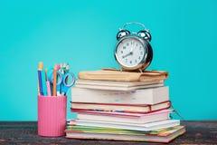 πίσω σχολείο έννοιας Βιβλία, χρωματισμένα μολύβια και ρολόι Στοκ εικόνα με δικαίωμα ελεύθερης χρήσης