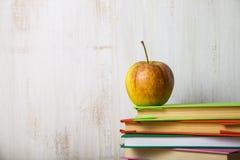 πίσω σχολείο Apple σε έναν σωρό των βιβλίων σε έναν ελαφρύ ξύλινο πίνακα Στοκ Εικόνα
