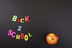Πίσω 2 σχολικές ζωηρόχρωμες επιστολές και ένα μήλο στο υπόβαθρο πινάκων με το copyspace για το κείμενό σας Έννοια για το σας Στοκ Εικόνες