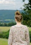 Πίσω της ξανθής νέας γυναίκας εξετάστε τη θέα βουνού στο πουλόβερ Στοκ Εικόνες