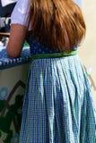 Πίσω του θηλυκού με τη μακριά κόκκινη τρίχα στο γερμανικό φόρεμα ύφους Στοκ Εικόνες
