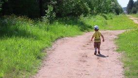 Πίσω του μικρού παιδιού που πηγαίνει στη δασική πορεία μεταξύ της πράσινης χλόης απόθεμα βίντεο