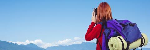 Πίσω του χιλιετούς backpacker με τη κάμερα ενάντια στη σειρά ουρανού και βουνών Στοκ φωτογραφία με δικαίωμα ελεύθερης χρήσης