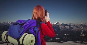 Πίσω του χιλιετούς backpacker με τη κάμερα ενάντια στη χιονώδη σειρά βουνών Στοκ Εικόνα