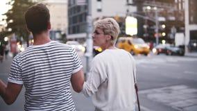 Πίσω χέρια εκμετάλλευσης περιπάτων ζευγών άποψης σε αργή κίνηση ευτυχή νέα κατά μήκος της όμορφης οδού στην πόλη της Νέας Υόρκης  απόθεμα βίντεο