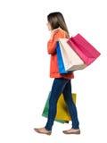 Πίσω όψη της πηγαίνοντας γυναίκας με τις τσάντες αγορών όμορφο κορίτσι ι Στοκ Εικόνες