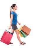 Πίσω όψη της πηγαίνοντας γυναίκας με τις τσάντες αγορών όμορφο κορίτσι ι Στοκ εικόνες με δικαίωμα ελεύθερης χρήσης