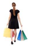Πίσω όψη της πηγαίνοντας γυναίκας με τις τσάντες αγορών Στοκ Εικόνα