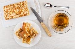 Πίτα βανίλιας με την κρέμα, κουταλάκι του γλυκού, μαχαίρι κουζινών, φλυτζάνι του τσαγιού Στοκ Εικόνα