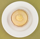 Πίτα λεμονιών, άσπρο πιάτο, πράσινο υπόβαθρο Στοκ εικόνα με δικαίωμα ελεύθερης χρήσης