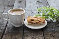 Πίτα και φλιτζάνι του καφέ της Apple με τα λουλούδια στον πίνακα Στοκ Φωτογραφία