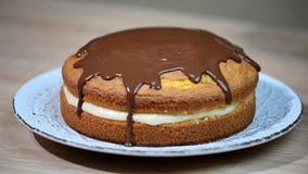 Πίτα κρέμας της Βοστώνης με την τοποθέτηση υαλοπινάκων σοκολάτας Χύνοντας σοκολάτα ganache σε μια πίτα κρέμας της Βοστώνης απόθεμα βίντεο