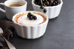 Πίτα με την πλήρωση φρούτων και μούρων και μαρέγκα με ένα φλιτζάνι του καφέ σε ένα μαύρο υπόβαθρο Στοκ Εικόνες