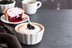 Πίτα με την πλήρωση φρούτων και μούρων και μαρέγκα με ένα φλιτζάνι του καφέ σε ένα μαύρο υπόβαθρο Στοκ Φωτογραφία
