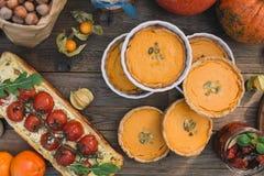 Πίτα με τις ντομάτες κερασιών, πίτα κολοκύθας, πορτοκάλι και τσάντα εγγράφου με τα καρύδια Στοκ Εικόνες