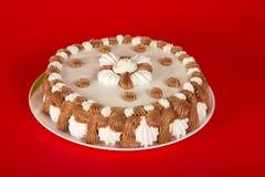 Πίτα σε ένα πιάτο, που διακοσμείται με την κρέμα Στοκ Εικόνες