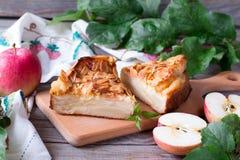 Πίτα της Apple και κόκκινα μήλα σε έναν ξύλινο πίνακα Στοκ Φωτογραφίες