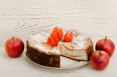 Πίτα της Apple και ώριμα μήλα σε έναν ελαφρύ ξύλινο πίνακα Στοκ εικόνες με δικαίωμα ελεύθερης χρήσης