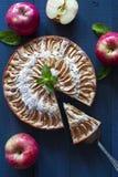 Πίτα της Apple με ένα κομμάτι στο μπλε βαθύ υπόβαθρο Στοκ Φωτογραφίες