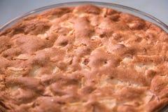 Πίτα της Apple με μια χρυσή κρούστα σε ένα στρογγυλό τηγάνι γυαλιού Στοκ Εικόνες