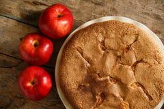 Πίτα της Apple με τα μήλα στο ξύλινο υπόβαθρο Στοκ Φωτογραφία