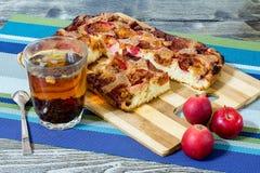 Πίτα της Apple με την κανέλα και ένα φλυτζάνι του τσαγιού σε έναν ξύλινο πίνακα Στοκ εικόνα με δικαίωμα ελεύθερης χρήσης