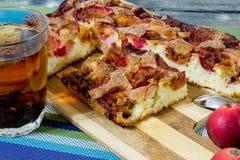 Πίτα της Apple με την κανέλα και ένα φλυτζάνι του τσαγιού σε έναν ξύλινο πίνακα Στοκ Εικόνα