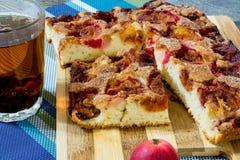 Πίτα της Apple με την κανέλα και ένα φλυτζάνι του τσαγιού σε έναν ξύλινο πίνακα Στοκ Φωτογραφίες