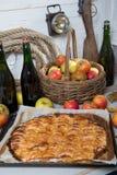 Πίτα της Apple με το καλάθι των μήλων και το μπουκάλι του μηλίτη Στοκ εικόνα με δικαίωμα ελεύθερης χρήσης